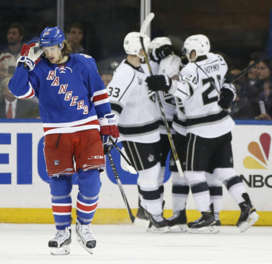 New York Rangers Carl Hagelin (62), left, reacts as the Los Angeles Kings Willie Mitchell (33) and Slava Voynov (26), celebrate a second period goal by Mike Richards, center, during Game 3 of the NHL hockey Stanley Cup Final, Monday, June 9, 2014, in New York. (AP Photo/Kathy Willens)