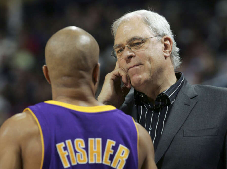 """FILE - In this Nov. 1, 2008 file photo, Los Angeles Lakers coach Phil Jackson talks with Derek Fisher during the second half of an NBA basketball game against the Denver Nuggets in Denver. Fisher has agreed to become the next coach of the New York Knicks and will be introduced at a news conference Tuesday morning, June 10, 2014, a person familiar with the situation told The Associated Press. The Knicks did not confirm the hiring, other than saying they were planning a """"major announcement. Jackson is now the Knicks president. (AP Photo/Jack Dempsey, File)"""