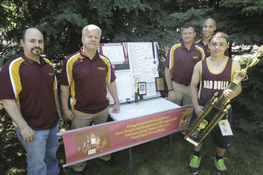 Hour photo/ Matthew VinciNorwalk Mad Bulls wrestler Jeff Cocchia, on right in singlet, poses with his four coaches, from left, David Slapin, Art Schad, Randy Hous and Jason Singer, and wrestling trophies.