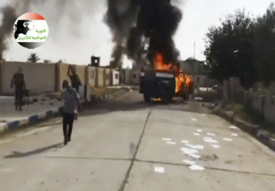 This image made from video posted by Iraqi0Revolution, a group supporting the al-Qaida breakaway Islamic State of Iraq and the Levant (ISIL) on Wednesday, June 12, 2014, which has been verified and is consistent with other AP reporting, shows militants on Al-Sharqat base north of Tikrit, Iraq. The al-Qaida-inspired group that led the charge in capturing two key Sunni-dominated cities in Iraq this week has vowed to march on to Baghdad, raising fears about the Shiite-led government's ability to slow the assault following lightening gains. Fighters from ISIL on Wednesday took Saddam Hussein's hometown of Tikrit, as soldiers and security forces abandoned their posts and yielded ground once controlled by U.S. forces. (AP Photo/Iraqi0Revolution via AP video)