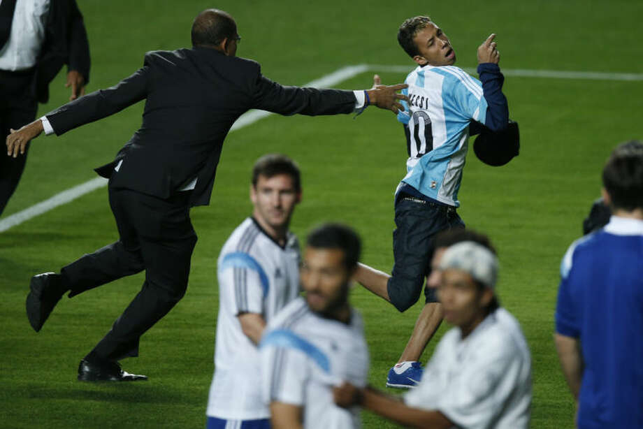 A security guard fails to stop a fan who invaded the pitch wearing an Argentine jersey, top, as Argentina's Lionel Messi, center, and other players look on at the end of a training session at Independencia Stadium in Belo Horizonte, Brazil, Wednesday, June 11, 2014. Argentina will play in group F of the Brazil 2014 soccer World Cup. (AP Photo/Victor R. Caivano)