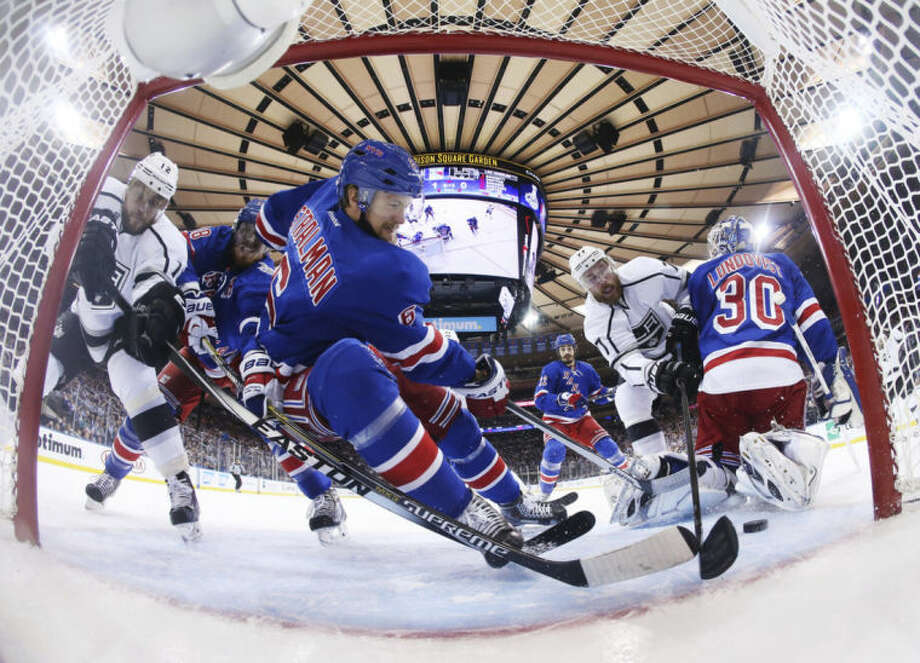 New York Rangers defenseman Anton Stralman (6) saves the puck from crossing the goal line as Los Angeles Kings center Jeff Carter (77) tries to score from behind New York Rangers goalie Henrik Lundqvist (30) in the first period during Game 4 of the NHL hockey Stanley Cup Final, Wednesday, June 11, 2014, in New York. (AP Photo/Bruce Bennett, Pool)