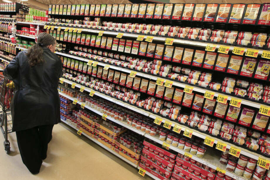FILE - This Feb. 7, 2012 file photo shows a shopper walking down the canned soup aisle at a grocery store in Cincinnati. Food companies and restaurants could soon face government pressure to make their foods less salty _ a long-awaited federal effort to try and prevent thousands of deaths each year from heart disease and stroke. (AP Photo/Al Behrman, File)