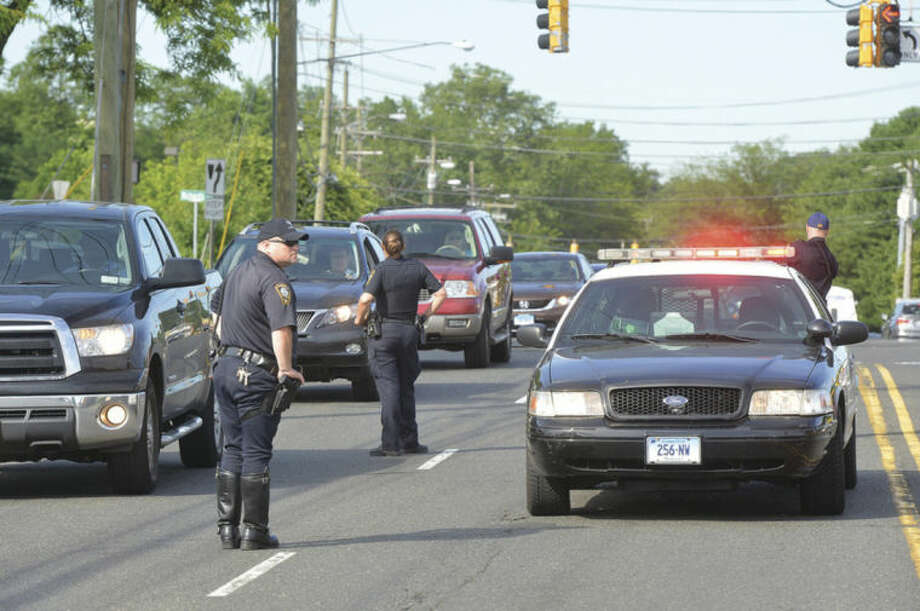 Hour Photo/Alex von Kleydorff Traffic flows northbound while police from Norwalk New Canaan and Wilton which are part of the multi-agency traffic safety task force set up a distracted driving check point on Connecticut Ave Monday morning.