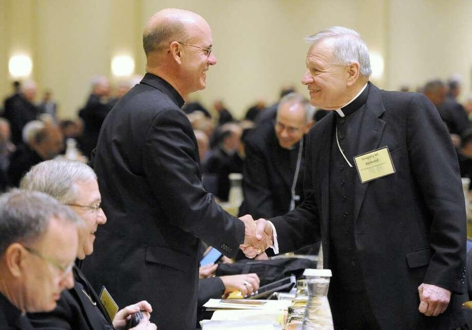 Bishop Kevin C. Rhoades, left, of Fort Wayne-South Bend, Ind.,and Archbishop Gregory M. Aymond of New Orleans shake hands at the start of a U.S. Conference of Catholic Bishops general meeting at the conference's annual fall meeting in Baltimore Monday, Nov. 10, 2014. (AP Photo/Steve Ruark)