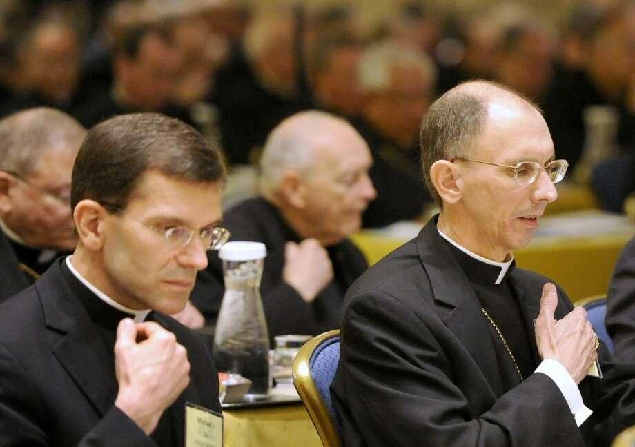 Bishop Michael J. Sis, left, of San Angelo, Texas and Bishop Peter J. Jugis, right, of Charlotte, N.C., pray at the U.S. Conference of Catholic Bishops annual fall meeting in Baltimore, Monday, Nov. 10, 2014. (AP Photo/Steve Ruark)
