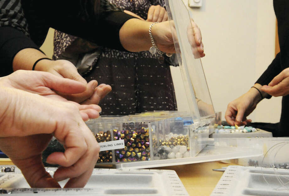 Hour photo/Matthew VinciStudents pick through all styles of beads Sunday at South Norwalk's master bead class.