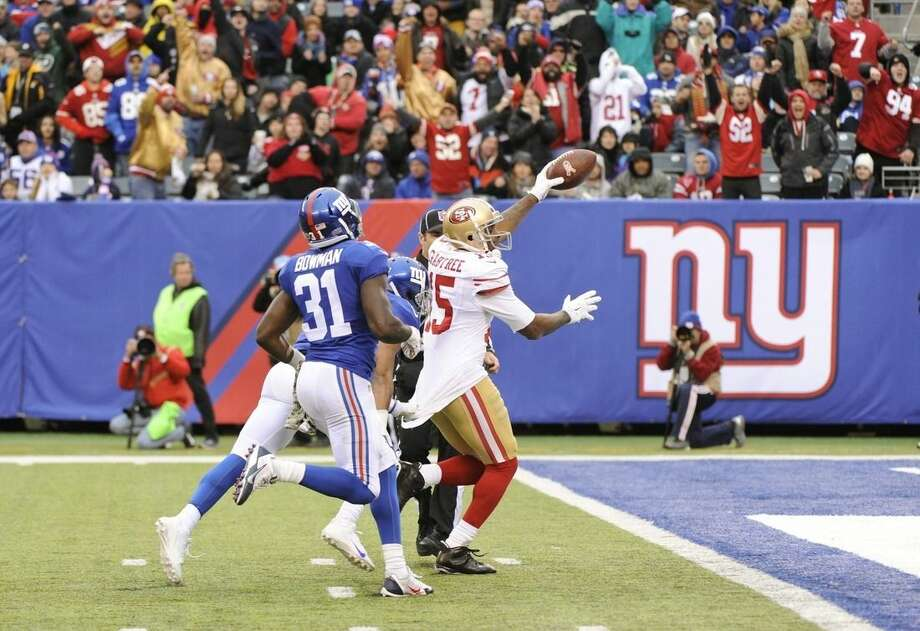 San Francisco 49ers wide receiver Michael Crabtree (15) runs away from New York Giants' Zack Bowman (31) for a touchdown as fans cheer during the second half of an NFL football game Sunday, Nov. 16, 2014, in East Rutherford, N.J. (AP Photo/Bill Kostroun)