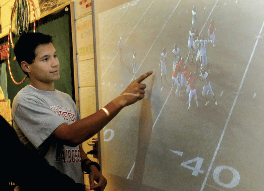 Hour photo/Matthew VinciNorwalk High School football player Brendan Brown points out a play using the computer website Hudl on the big screen in football coach Pat Moffet's classroom.