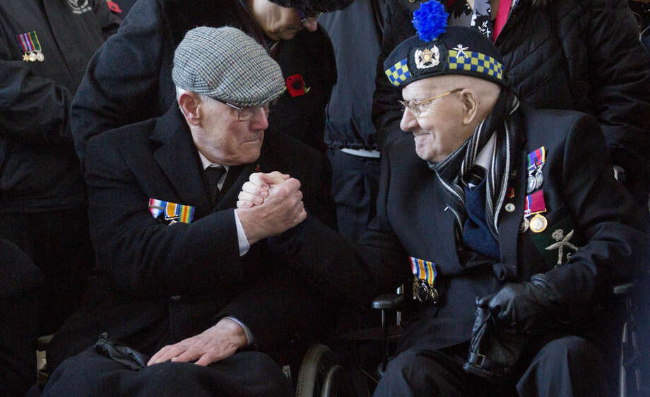 British World War II veterans David Ovenstone, right, and Leslie Potter hold hands during an Armistice Day ceremony at the Menin Gate in Ypres, Belgium on Tuesday, Nov. 11, 2014. The Menin Gate Memorial bears the names of more than 54,000 British and Commonwealth soldiers who were killed in the Ypres Salient of World War I and whose graves are not known. Ovenstone's father served in WWI with the Royal Army and was gassed and wounded on the Somme in 1915. Potter's grandfather was killed in Nov. 1915 and his name is engraved on the Menin Gate. (AP Photo/Virginia Mayo)
