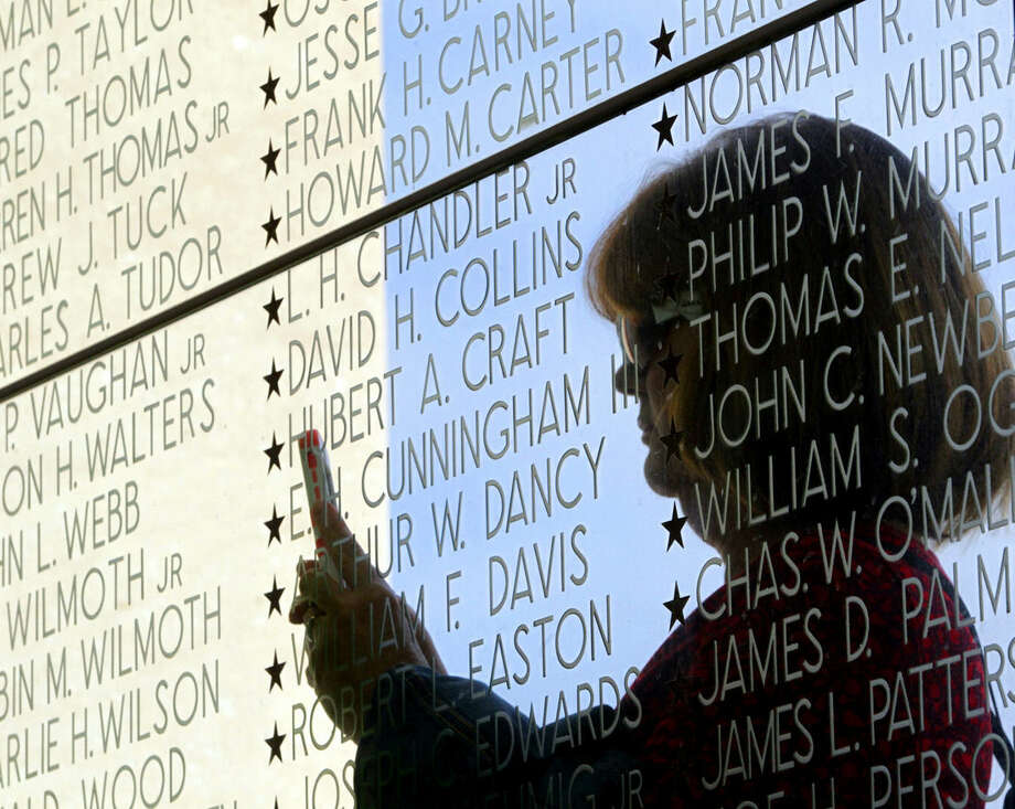 Retired Navy Capt. Mary Lou Wassel, a Navy nurse, is reflected in Through the Wall of Memory, glass etched with the names of fallen Virginia soldiers, while taking a photograph during Veterans Day ceremonies at the Virginia War Memorial in Richmond, Va., Tuesday, Nov. 11, 2014. (AP Photo/The Richmond Times-Dispatch, Joe Mahoney)