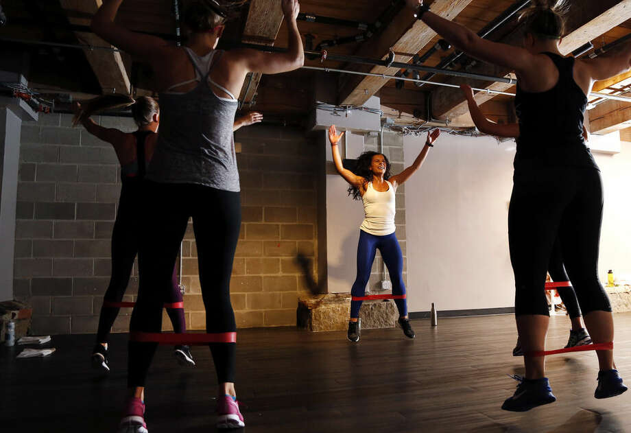 """In this Oct. 30, 2014 photo, Kelly Brabants, rear center, leads her """"Booty by Brabants"""" class at The Club by George Foreman III gym in Boston. The class, started by Brabants a year ago, fits in 120 squats in 45 minutes. (AP Photo/Elise Amendola)"""
