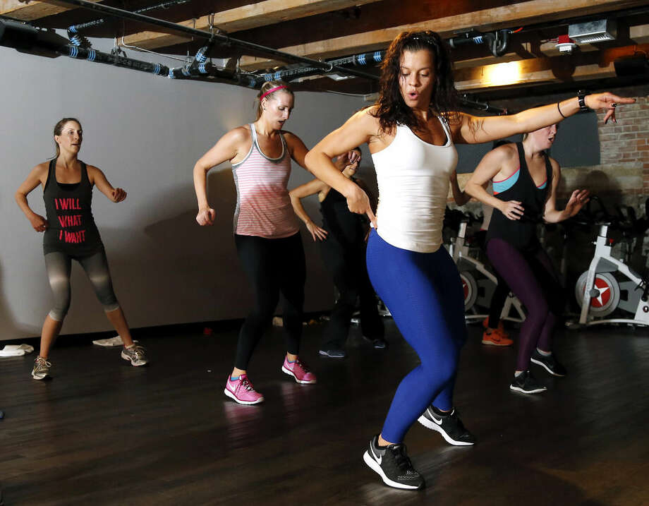 """In this Oct. 30, 2014 photo, Kelly Brabants, foreground, leads her """"Booty by Brabants"""" class at The Club by George Foreman III gym in Boston. The class, started by Brabants a year ago, fits in 120 squats in 45 minutes. (AP Photo/Elise Amendola)"""