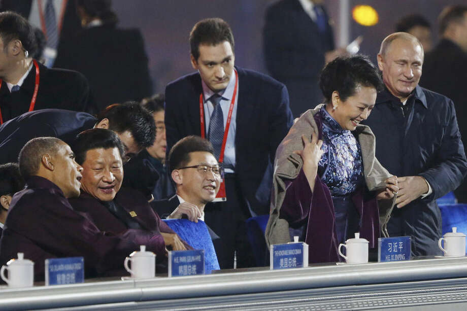 In this Nov. 10, 2014 file photo, Russia's President Vladimir Putin, right, puts a shawl on Peng Liyuan, second right, wife of Chinese President Xi Jinping, seated second left talking to U.S. President Barack Obama, left, as they arrive to watch a fireworks show after a welcome banquet for the Asia Pacific Economic Cooperation (APEC) summit in Beijing. It was a warm gesture on a chilly night when Vladimir Putin wrapped a shawl around the wife of Xi Jinping while the Chinese president chatted with Barack Obama. The only problem: Putin came off looking gallant, the Chinese summit host gauche and inattentive. (AP Photo, File) CHINA OUT