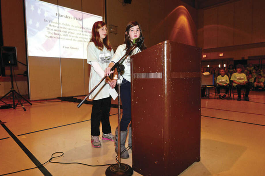 Hour photo / Erik Trautmann Cider Mill 5th graders Ariella Hatenbach and Hayley Sayewitz read the poem Flanders Fields during a Veteran's Day ceremony at Cider Mill Elementary School in Wilton Tuesday.