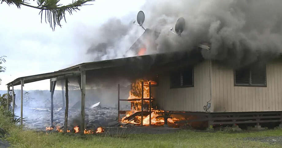 In this image made from video provided by the County of Hawaii, lava flow from the Kilauea Volcano burns a residential structure Monday, Nov. 11, 2014, in Pahoa, Hawaii. A stream of lava set a home on fire Monday in a rural Hawaii town that has been watching the slow-moving flow approach for months. The molten rock hit the house just before noon. The home's renters already had left the residence in Pahoa, the largest town in the Big Island's isolated and mostly agricultural Puna district. (AP Photo/County of Hawaii)