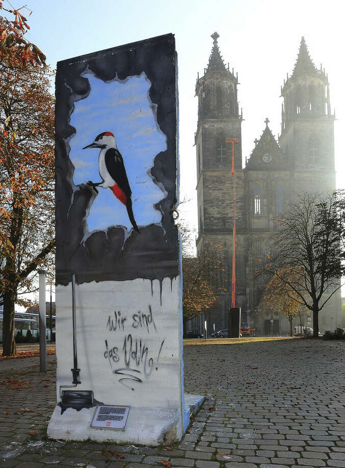 This picture taken Oct. 29, 2014 shows a segment of the Berlin Wall in front of the Magdeburg, eastern Germany, cathedral. The wall that once separated East from West Berlin has largely disappeared from the city. The few sections that remain stand as potent monuments to the ideological divisions of the Cold War. But 25 years after the Berlin Wall fell, some 120 parts of it can now be found in more than 40 countries, from Britain to South Africa and the United States. (AP Photo/DPA, Jens Wolf)