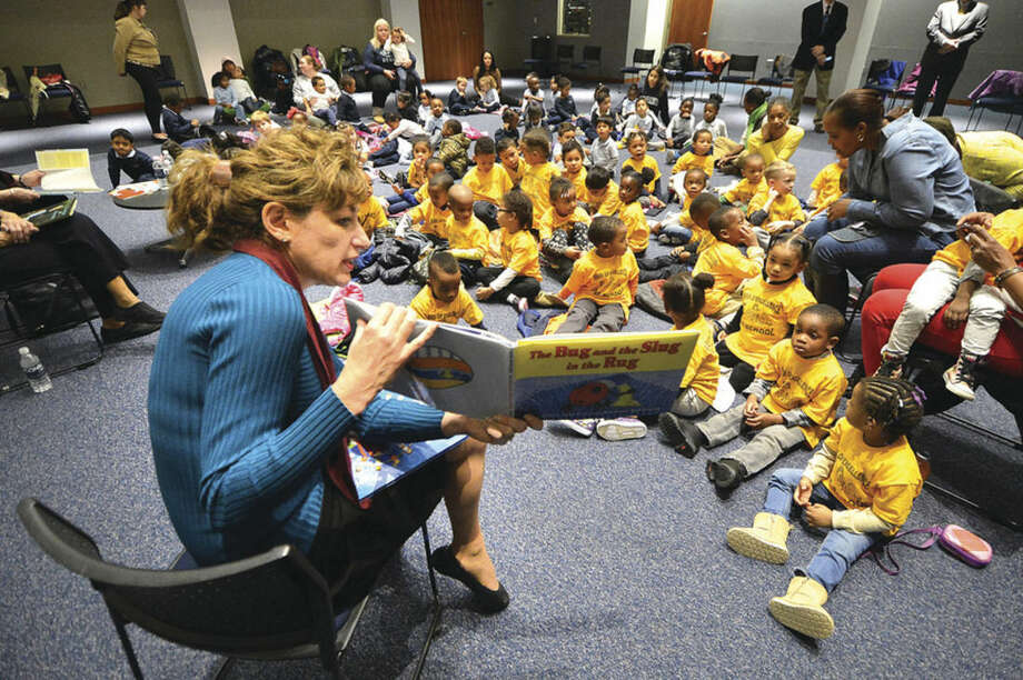 Hour photo/Alex von KleydorffUConn President Susan Herbst reads 'The Bug, The Slug in the Rug' to kids during its annual reading day at UConn Stamford Thursday.