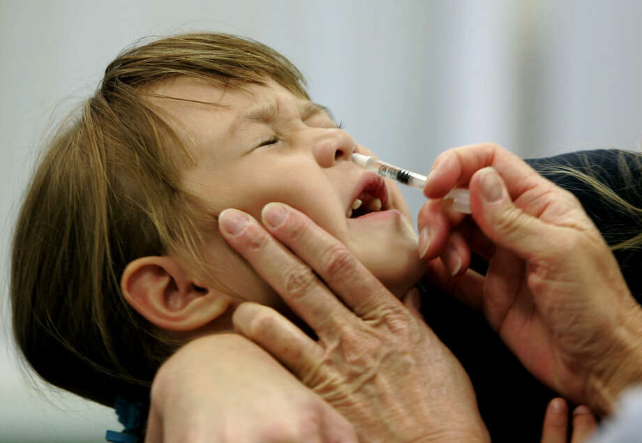 FILE- In this Oct. 4, 2005, file photo, a toothless Danielle Holland reacts as she is given a FluMist influenza vaccination in St. Leonard, Md. The Centers for Disease Control and Prevention issued a statement Thursday, Nov. 6, 2014, reacting to startling new data that the nasal spray vaccine made by AstraZeneca's subsidiary MedImmune was ineffective last winter against swine flu. (AP Photo/Chris Gardner, File)