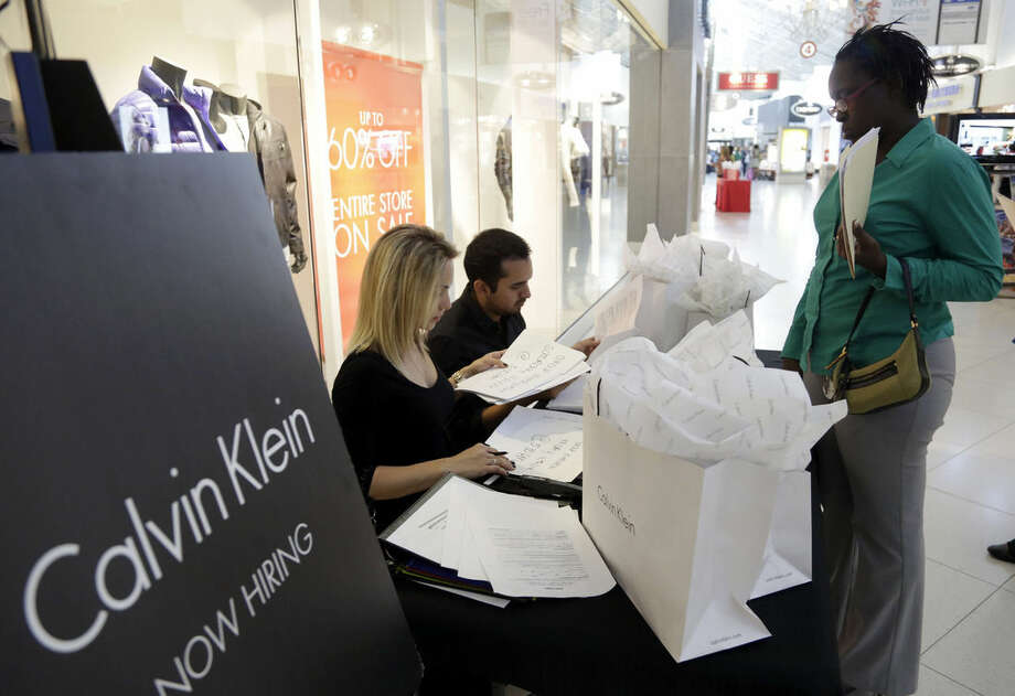 In this Oct. 28, 2014 photo, Shantel Howard, 29, of Miami, right, makes an appointment for a job interview with Calvin Klein employee Melina Mikhalices, left, after submitting her resume during a job fair at Dolphin Mall, in Miami. The Labor Department releases employment data for October on Friday, Nov. 7, 2014. (AP Photo/Lynne Sladky)