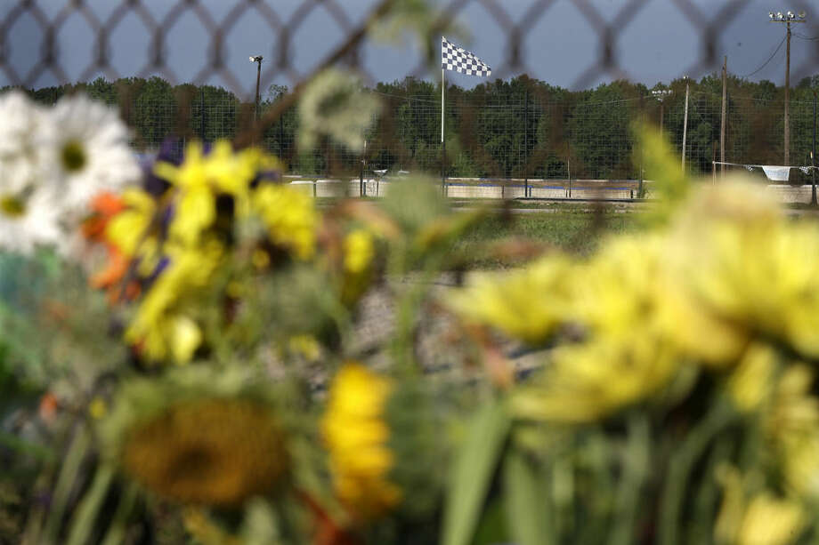 "A checkered flag flies over the track near a small memorial of flowers at Canandaigua Motorsports Park Monday, Aug. 11, 2014, in Canandaigua, N.Y. On Saturday night, Tony Stewart struck and killed Kevin Ward Jr., 20, a sprint car driver who had climbed from his car and was on the track trying to confront Stewart during a race at the track in upstate New York. Ontario County Sheriff Philip Povero said his department's investigation is not criminal and that Stewart was ""fully cooperative"" and appeared ""very upset"" over what had happened. (AP Photo/Mel Evans)"