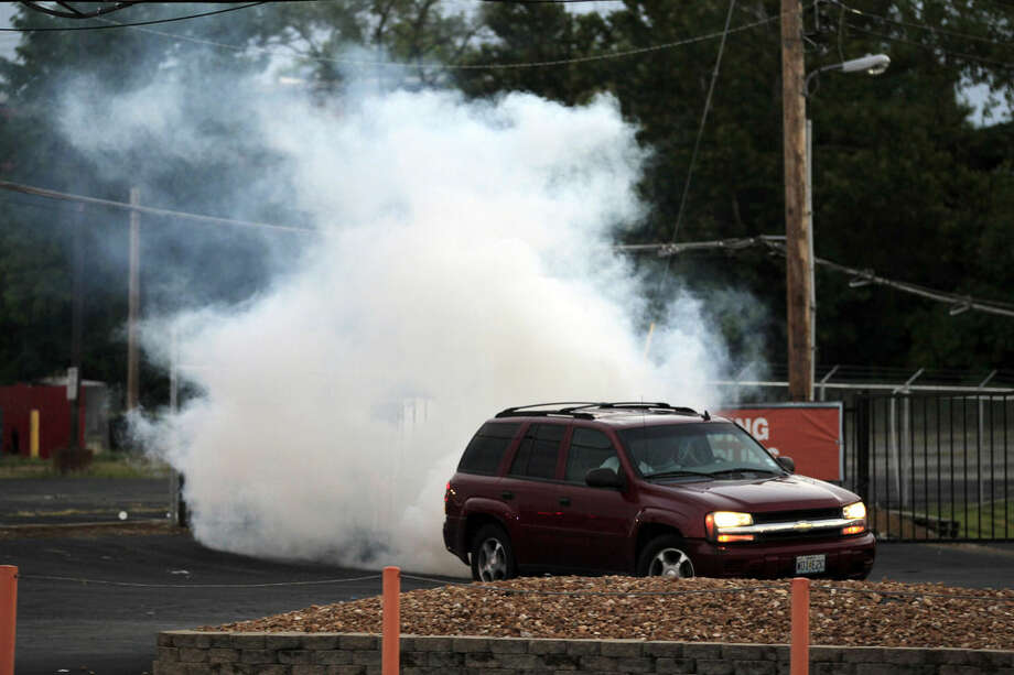 A car pulls away as tear gas is deployed by police Monday, Aug. 11, 2014, in Ferguson, Mo. The FBI opened an investigation Monday into the death of 18-year-old Michael Brown, who police said was shot multiple times Saturday after being confronted by an officer in Ferguson. Authorities in Ferguson used tear gas and rubber bullets to try to disperse a large crowd Monday night that had gathered at the site of a burned-out convenience store damaged a night earlier, when many businesses in the area were looted. (AP Photo/Jeff Roberson)