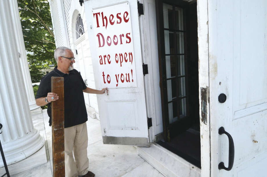 Hour photo/Alex von KleydorffThe Rev. Frank Newsome opens the front doors to the First Congregational Church.