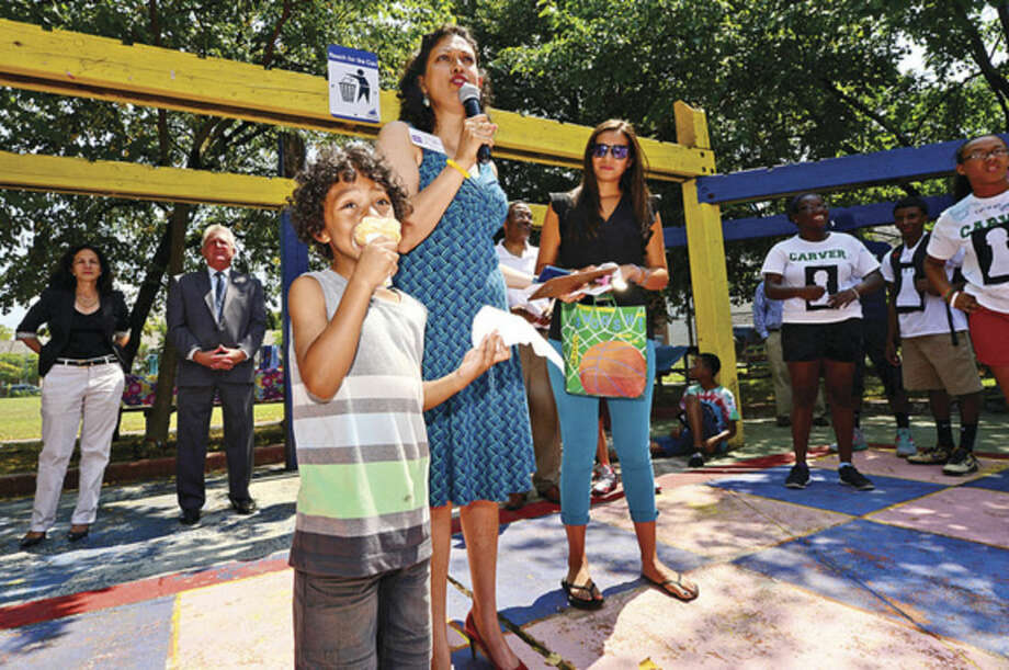 Hour photo / Erik Trautmann Carver Foundation Summer camper Amir Walken, 5, receives his award from Councilwomen Anna Duleep and Eloisa Melendez during the Friends of Ryan Park Summer Camper Awards celebration at the Park Friday afternoon. The Carver Foundation runs summer programs for more than 600 Norwalk children.