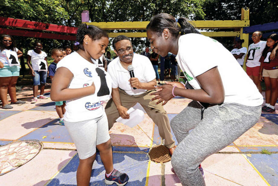 Hour photo / Erik Trautmann Carver Foundation Summer camper Julia Otero, 6, is met by counselor Jaid Addison as CT Representative Bruce Morris (D-140) announces the opening move in a game of human chess which pitted campers against staff during the Friends of Ryan Park Summer Camper Awards celebration at the Park Friday afternoon. The Carver Foundation runs summer programs for more than 600 Norwalk children.