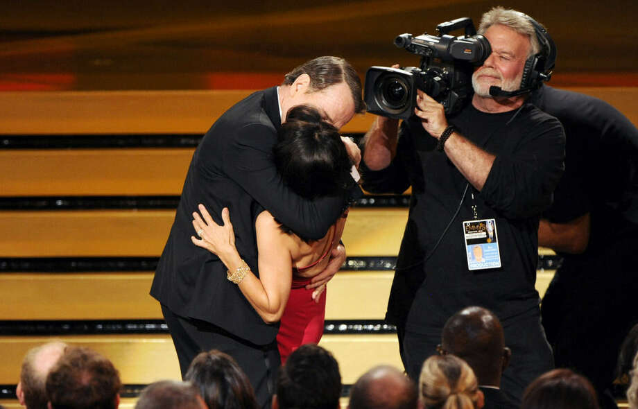 """Bryan Cranston kisses Julia Louis-Dreyfus, center front, as she accepts the award for outstanding lead actress in a comedy series for her work on """"Veep"""" at the 66th Annual Primetime Emmy Awards at the Nokia Theatre L.A. Live on Monday, Aug. 25, 2014, in Los Angeles. (Photo by Chris Pizzello/Invision/AP)"""