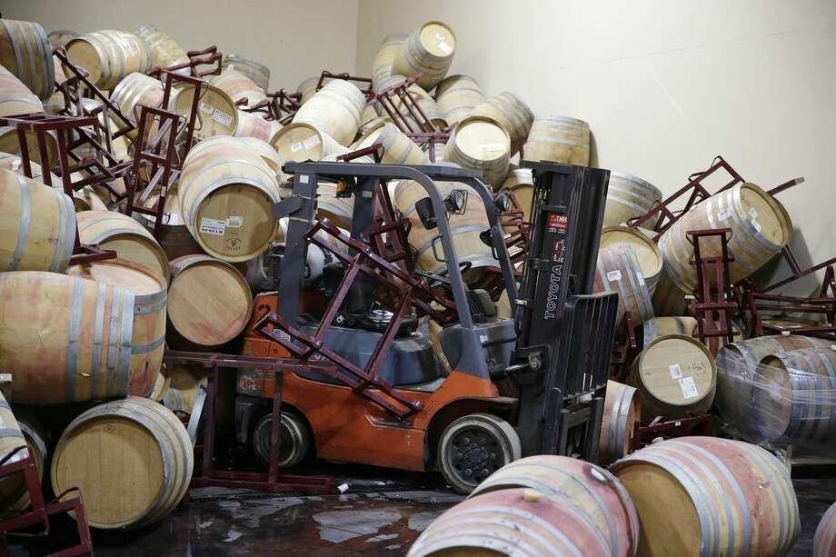 A forklift is partially buried in some of the hundreds of earthquake damaged wine barrels at the Kieu Hoang Winery Monday, Aug. 25, 2014, in Napa, Calif. A powerful earthquake that struck the heart of California's wine country caught many people sound asleep, sending dressers, mirrors and pictures crashing down around them and toppling wine bottles in vineyards around the region. The magnitude-6.0 quake struck at 3:20 a.m. PDT Sunday near the city of Napa. (AP Photo/Eric Risberg)