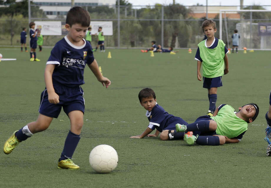 In this Thursday, Aug. 1, 2014 photo, Toby Rafique, 6, right, of Dallas, yells as he falls to the ground during a soccer camp held by FC Barcelona in Miami. European clubs like Barcelona, Liverpool and Arsenal have long sent coaches to work at U.S. summer camps, but now some are opening year-round U.S. academies aimed at finding new talent but also to expand their fan bases. This is part of a number of initiatives of major teams to grow their brands in the U.S. (AP Photo/Lynne Sladky)
