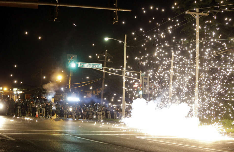 A device deployed by police goes off in the street as police and protesters clash Wednesday, Aug. 13, 2014, in Ferguson, Mo. Authorities in the St. Louis suburb where an unarmed black teen was shot and killed by a police officer have used tear gas to try to disperse protesters after flaming projectiles were thrown from the crowd. (AP Photo/Jeff Roberson)