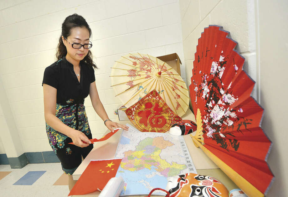 Hour Photo/Alex von Kleydorff Teacher Wei Wei from China is sets out some items from China to bring a little of her home to the students at Roton Middle School