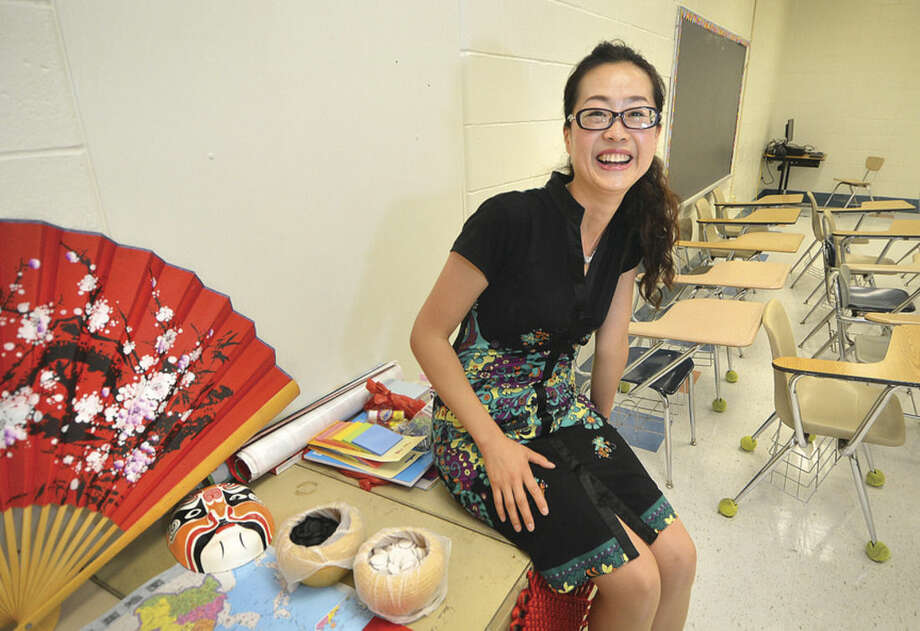 Hour Photo/Alex von Kleydorff Teacher Wei Wei from China is happy to start making this classroom at Roton Middle School hers for the next school year.