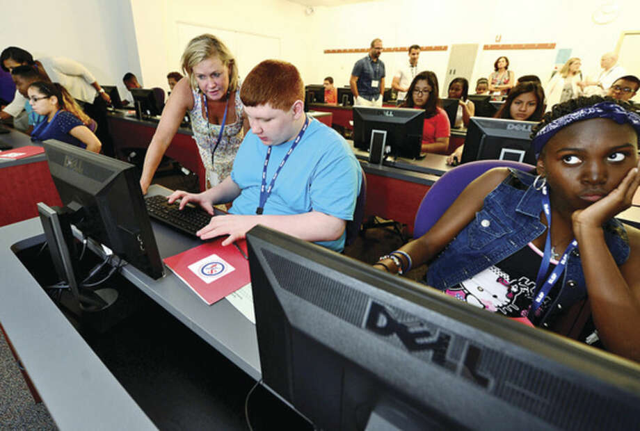 Hour photo / Erik Trautmann Incoming high school freshmen including Benny Pisanelli and Montez Mayo learn the Naviance computer platform with the help of Westhill guidance counselor Mairead Collins at the UCONN Stamford campus Tuesday as part of the Stamford Achieves pilot summer bridge program that prepares students for the first year of high school.