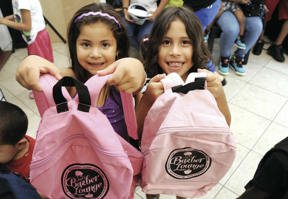 Hour photo/Matthew VinciOlivia Serrano and her cousin Samarif, both 6, hold their new Joel's backpacks for the back-to-school drive held at Joel's Barber Lounge in Norwalk on Sunday.