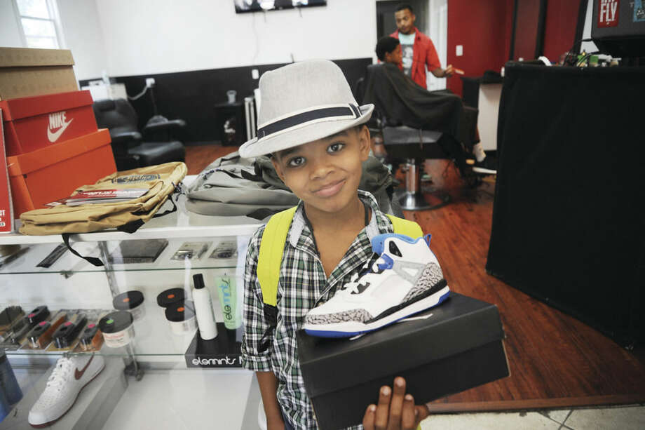 Hour photo/Matthew VinciDamari Maxem, 6, won a new pair of sneakers in a raffle for the first day of school at Joel's Barber Lounge for the back-to-school drive in Norwalk on Sunday.