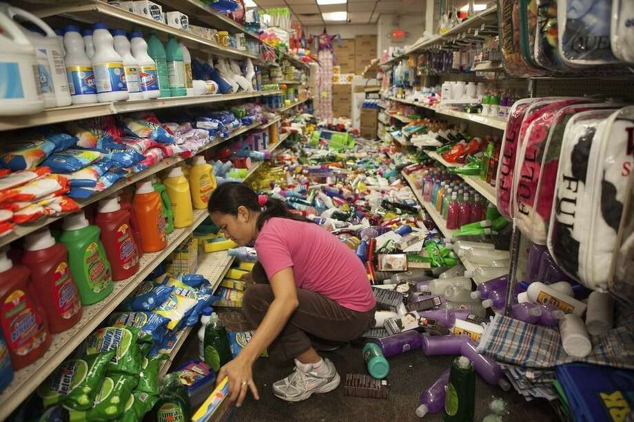 Nina Quidit cleans up the Dollar Plus and Party Supplies Store in American Canyon Calif., after an earthquake on Sunday, Aug. 24, 2014. Quidit and her husband were woken up in the early morning hours by the store's alarm company and immediately drove in to begin cleaning up. (AP Photo/Alex Washburn)