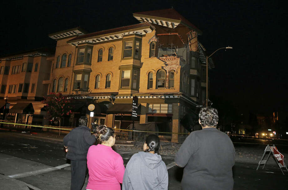 People look at a damaged building with a top corner exposed following an earthquake Sunday, Aug. 24, 2014, in Napa, Calif. A large earthquake rolled through California's northern Bay Area early Sunday, damaging some buildings, igniting fires, knocking out power to tens of thousands and sending residents running out of their homes in the darkness. (AP Photo/Eric Risberg)