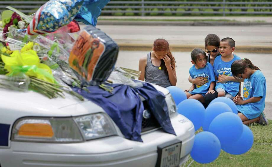 "Jennifer Damian, center, visits the memorial for Officer Endy Ekpanya with her children, from left, Arianna, 12; Jazmin, 4; Jaxon, 4; and Elysia, 8. Damian offered sympathy for Ekpanya's fiancée and young son. ""It just hits home,"" she said. Photo: Melissa Phillip, Staff / © 2016 Houston Chronicle"