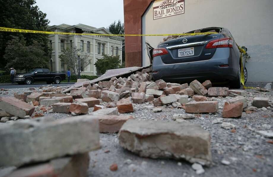 Bricks and fallen rubble cover a car with the old courthouse in the background following an earthquake Sunday, Aug. 24, 2014, in Napa, Calif. A large earthquake rolled through California's northern Bay Area early Sunday, damaging some buildings, igniting fires, knocking out power to tens of thousands and sending residents running out of their homes in the darkness. (AP Photo/Eric Risberg)