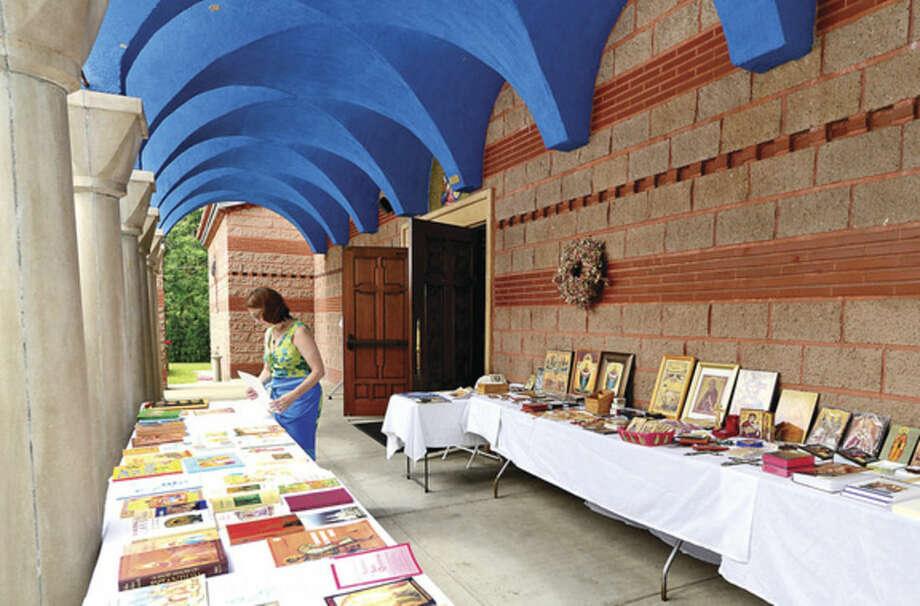 Hour photo / Erik Trautmann Volunteer Alicia Sprio organizes the iconography for sale at the St. George Greek Orthodox Church annual Greek festival Saturday.