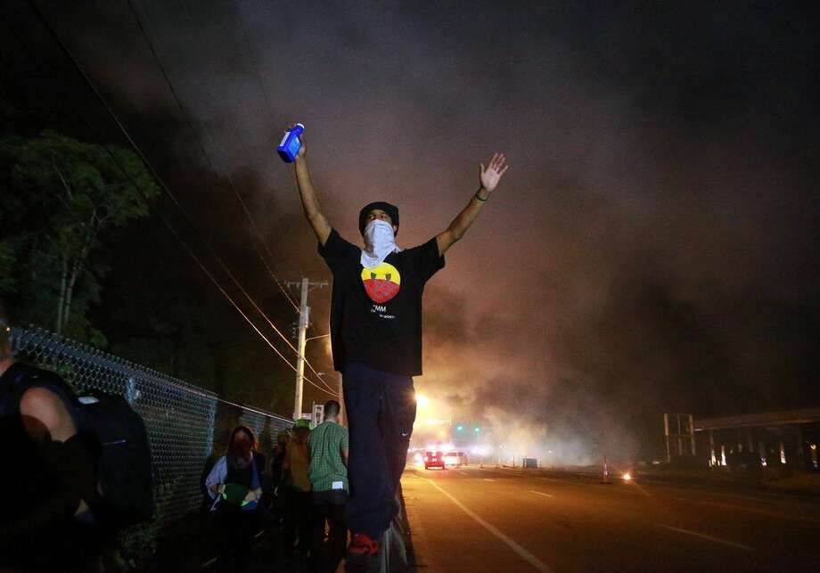 A protester raises his arms following a clash with police Monday, Aug. 18, 2014, in Ferguson, Mo. The Aug. 9 shooting of Michael Brown by police has touched off rancorous protests in Ferguson, a St. Louis suburb where police have used riot gear and tear gas. (AP Photo/St. Louis Post-Dispatch, Christian Gooden)