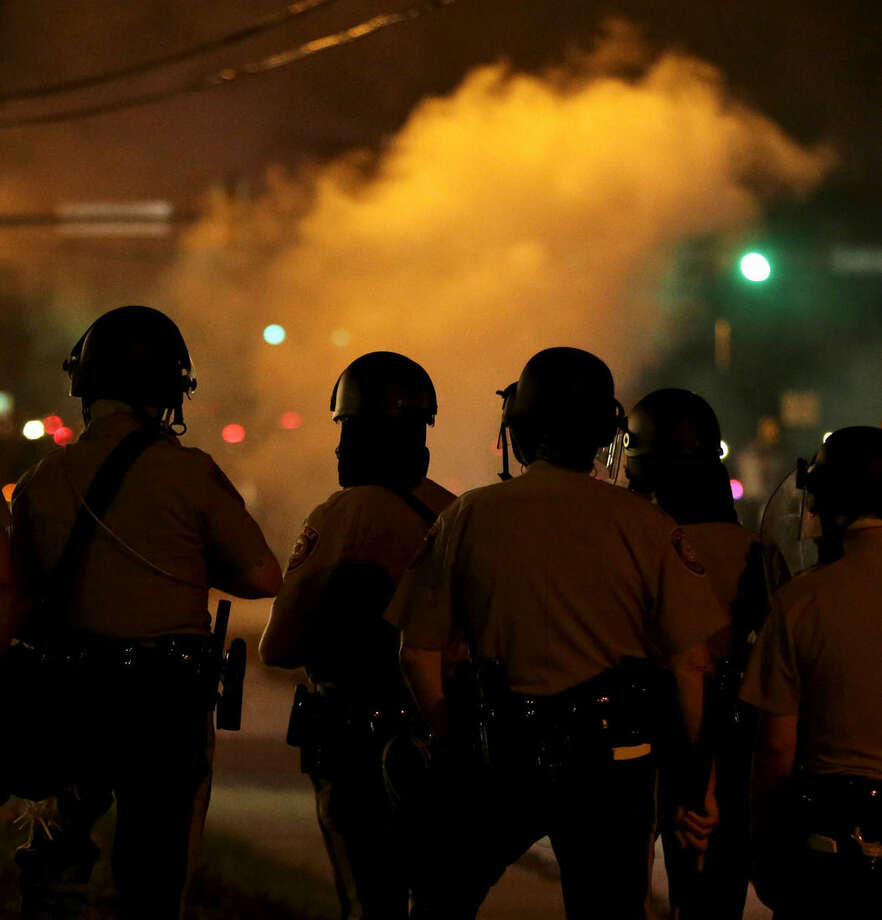 Police wait to advance after tear gas was used to disperse a crowd Sunday, Aug. 17, 2014, during a protest for Michael Brown who was killed by a police officer last Saturday in Ferguson, Mo. As night fell Sunday in Ferguson, another peaceful protest quickly deteriorated after marchers pushed toward one end of a street. Police attempted to push them back by firing tear gas and shouting over a bullhorn that the protest was no longer peaceful. (AP Photo/Charlie Riedel)