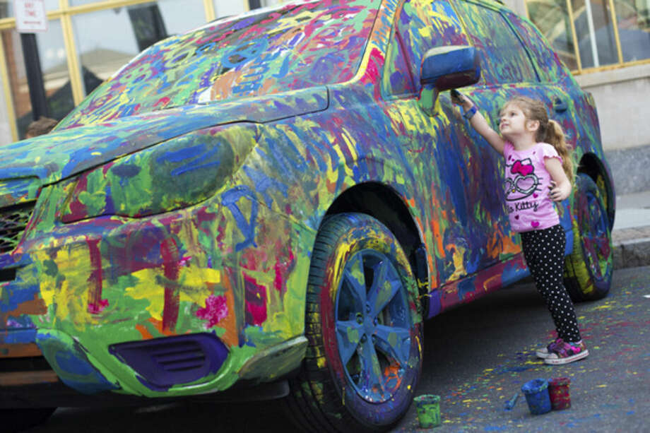 Above, Gracie Kerins, 3, of Norwalk, paints a car provided by Garavel Subaru at the 39th Annual SoNo Arts Festival Saturday afternoon. Lower left, the Funky Dawgz Brass Band performs on Washington Street at the festival. Lower right, Virginia Atkinson purchases some jewelry from Lise Weller of OMI by Lise.The celebration was first held in 1974 and kicked off a Renaissance for the South Norwalk business area, which was slated for demolition, according to Norwalk Mayor Harry Rilling. The festival hosts a diverse group of artists, musicians, dancers, children's entertainers and crafters in SoNo.