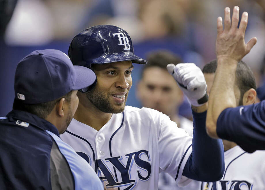 Tampa Bay Rays' James Loney, center, high fives teammates in the dugout after hitting a home run off New York Yankees relief pitcher Esmil Rogers during the eighth inning of a baseball game Friday, Aug. 15, 2014, in St. Petersburg, Fla. (AP Photo/Chris O'Meara)