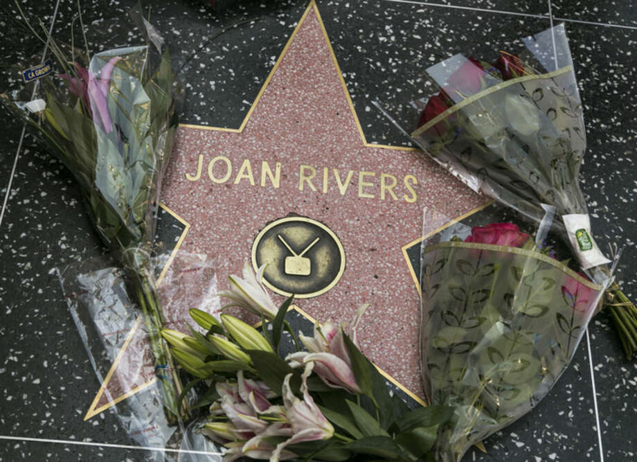 Flowers surround Joan Rivers' star on the Hollywood Walk of Fame in Los Angeles Thursday, Sept. 4, 2014. Rivers, the raucous, acid-tongued comedian who crashed the male-dominated realm of late-night talk shows and turned Hollywood red carpets into danger zones for badly dressed celebrities, died Thursday. She was 81. (AP Photo/Damian Dovarganes)