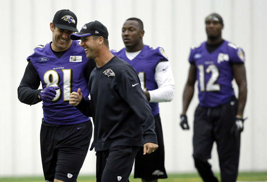 Baltimore Ravens tight end Owen Daniels, left, and head coach John Harbaugh laugh during an NFL football practice at the team's headquarters, Monday, Sept. 8, 2014, in Owings Mills, Md. Ravens running back Ray Rice was let go by the Ravens on Monday and suspended indefinitely by the NFL after a video was released showing the running back striking his then-fiancee in February. (AP Photo/Patrick Semansky)