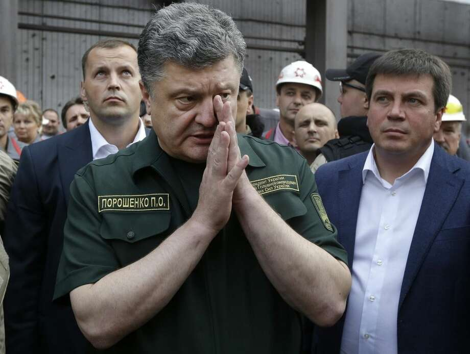 Ukrainian President Petro Poroshenko speaks to local workers during his visit to the Ilich Iron and Steel Works in the southern coastal town of Mariupol, Ukraine, Monday, Sept. 8, 2014. Poroshenko made a surprise trip Monday to a key city in southeastern Ukraine as a cease-fire between Russian-backed rebels and Ukrainian troops appeared to be largely holding. (AP Photo/Sergei Grits)